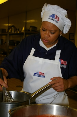 Rose St. John, 100th Services Squadron Gateway Dining Facility first cook, and Ministry of Defence employee, prepares teriyaki sauce Tuesday for the lunchtime special of teriyaki chicken. (U.S. Air Force photo by Karen Abeyasekere)