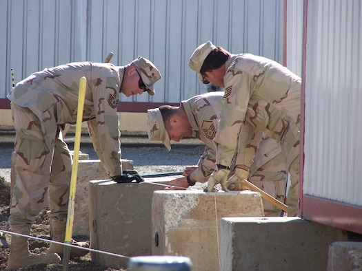 Kirkuk Regional Air Base, Iraq – (Left to Right) Tech. Sgt. Clay Bucy, Master Sgt. Will Jobson and Tech. Sgt. John LeMaster assigned to the 506th Expeditionary Civil Engineer Squadron level concrete footings for a Pod which will house base airman. Air Force reservists are deployed from the 445th Civil Engineer Squadron at Wright-Patterson AFB, Ohio. (U.S. Air Force curtsey photo).