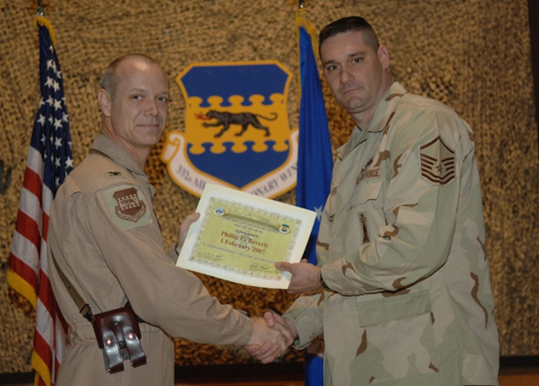 02/02/2007 -- SOUTHWEST ASIA -- Master Sgt. Philip Beverly, 35th Aircraft Maintenance Squadron, receives a certificiate from his deployed commander at Balad Air Base, Iraq. (U.S. Air Force photo)
