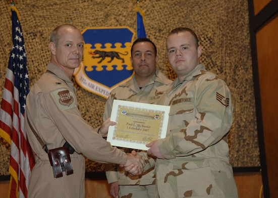 02/02/2007 -- SOUTHWEST ASIA -- Senior Airman Paul McDaniel, 35th Maintenance Operations Squadron, receives a certificiate from his deployed commander at Balad Air Base, Iraq. (U.S. Air Force photo)