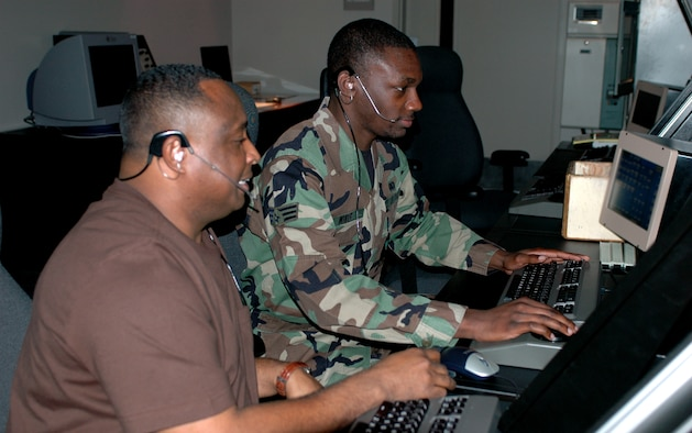 Senior Airman Donald White shows his uncle, Mr. Warren Richardson enhanced features on an air traffic control simulator. Both are air traffic controllers with the 60th Operations Support Squadron. (U.S. Air Force photo by Staff Sgt. Candy Knight)