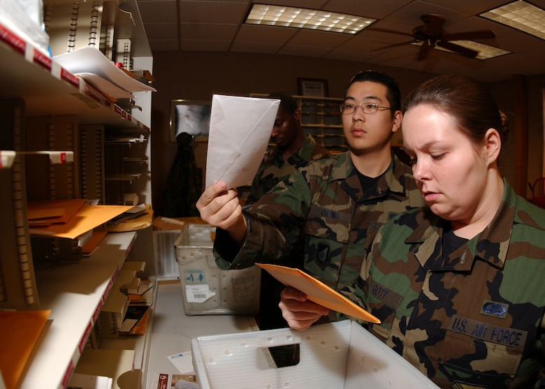 "EIELSON AIR FORCE BASE, Alaska -- Airman Ken Chung (Back) and Senior Airman Misty Gott (Front), 354th Communications Squadron, both pitch envelopes into mail boxes on Feb. 06. The base Mail Room on a daily basis will pick up, deliver and process over 500 pieces of mail.The mail is then ""pitched"", sorted, and proper postage is applied to all official mail.  (U.S. Air Force photo by Airman Jonathan Snyder)"