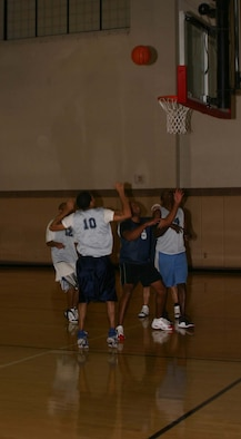 Players for the 264th Medical Battalion and the 365th Training Squadron surround the basket during the Feb. 7 game.  The 264th won the game, 77-73.