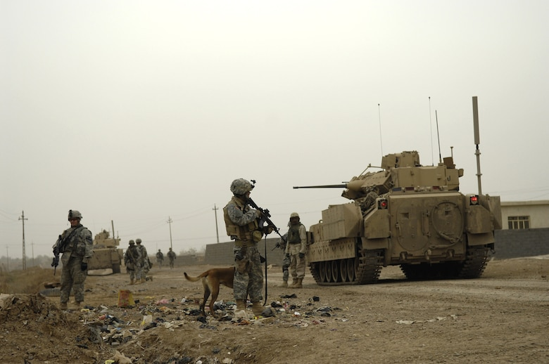 Tech. Sgt. Harvey Holt and his military working dog accompany Soldiers from the 1st Cavalry Division Feb. 6 during a patrol in Kahn Bani Sahd, Iraq.  Airmen continue to excel in nontraditional combat roles in support of combatant commanders' requirements where Airmen are deployed to assist Soldiers.  Sergeant Holt is assigned to the 732nd Expeditionary Security Forces Squadron.  (U.S. Air Force photo/Staff Sgt. Stacy L. Pearsall)