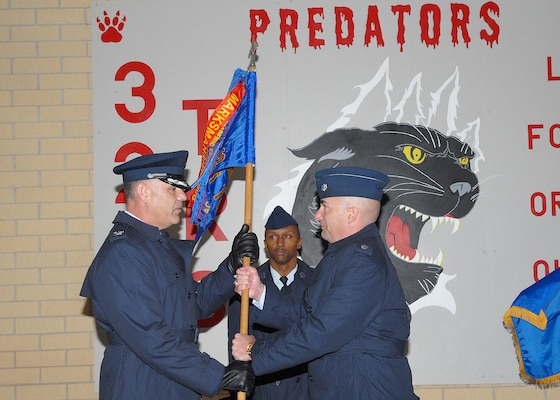 Col. Robert MacDonald, left, commander of the 737th Training Group at Lackland Air Force Base, Texas, receives the flag of the 321st Training Squadron from Lt. Col. Steve Cahanin during a Feb. 2 ceremony at the 321st TRS, which is temporarily standing down due to a current reduction in Air Force enlisted accessions. Colonel Cahanin, former 321st commander, now is commander of the 326th Training Squadron. (USAF photo by Robbin Cresswell)