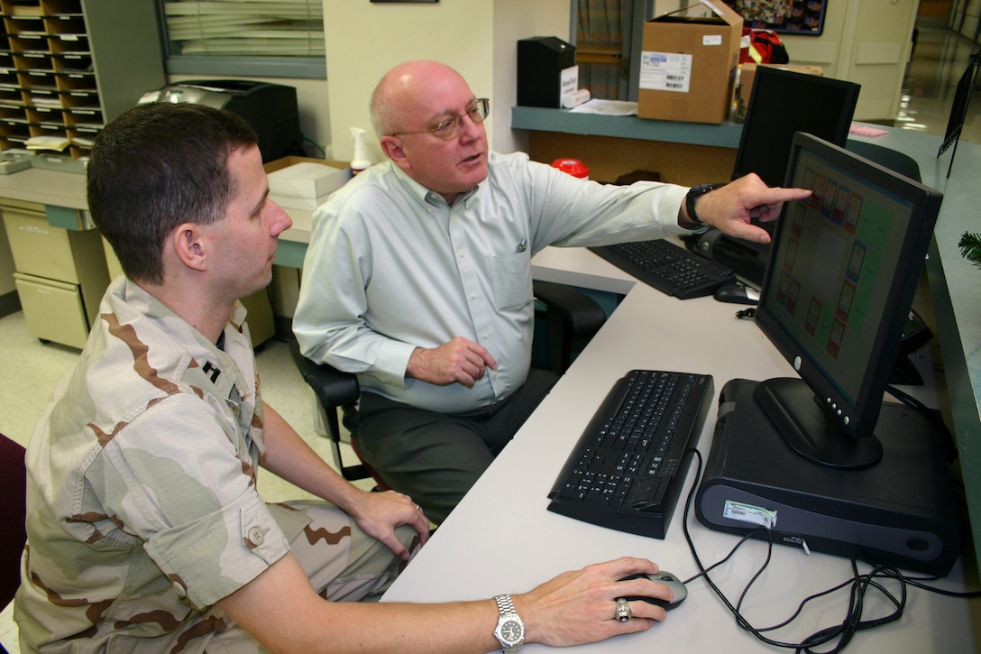 Capt. (Dr.) Allen Holder discusses graphical interface elements for a patient tracking system designed at Wilford Hall Medical Center with software engineer Ed Hander at Lackland Air Force Base, Texas. Now-Major Holder and Mr. Hander were key to the 59th Medical Wing being recognized during the annual TRICARE conference as a 2006 Department of Defense Patient Safety Award winner. (U.S. Air Force photo/Master Sgt. Kimberly Spencer)