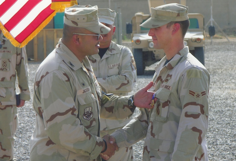Then, Airman 1st Class Jeremy Birchfield is presented the Purple Heart in a ceremony at Camp Victory, Iraq Sept. 24, 2006. The 824th Security Forces Squadron turret gunner was hit by a sniper during patrol operations Sept. 22, 2006. He is the first Airman from the 824th SFS to receive the medal. (U.S. Air Force photo/Staff Sgt. Jesse Smith)