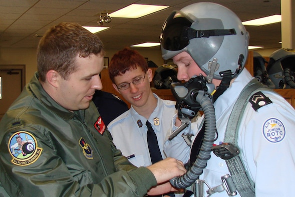 First Lt. Dave Ludington, 8th Flying Training Squadron instructor pilot, demonstrates an oxygen mask connection to Junior ROTC cadet Alex Owen while cadet William Payne looks on. Cadets from the Enid (Okla.) High School Junior ROTC detatchment visted the 8th FTS at Vance Air Force Base Feb. 8 as part of the squadron's heritage week Feb. 7 to 14. The event is part of Vance's year-long commemoration of the Air Force's 60th anniversary. (Photo by 2nd Lt. Agneta Murnan)
