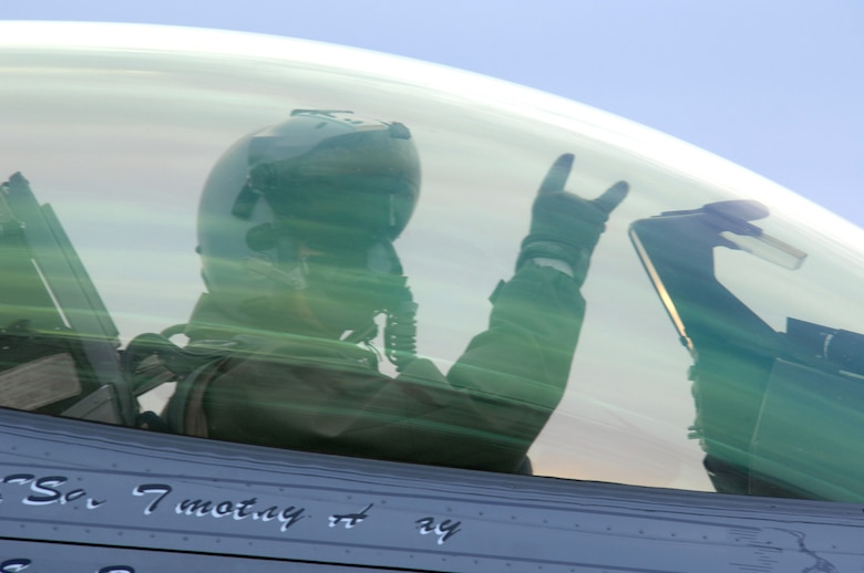 EIELSON AIR FORCE BASE, Alaska -- An F-16 Fighting Falcon pilot from the 18th Fighter Squadron signals from his aircraft prior to taking off for a training mission here on Feb.8. The 18th Fighter Squadron conducts air operations for combat-ready F-16 aircraft and provides close air support, forward air control (airborne), battlefield air interdiction, and offensive counter air.