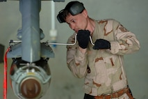 Staff Sgt. Steven Socia uses a speed wrench to secure a Joint Direct Attack Munition to an F-16 Fighting Falcon Feb. 7 at Balad Air Base, Iraq. Sergeant Socia is a weapons loader assigned to the 332nd Expeditionary Aircraft Maintenance Squadron.  (U. S. Air Force photo/Staff Sgt. Michael R. Holzworth)