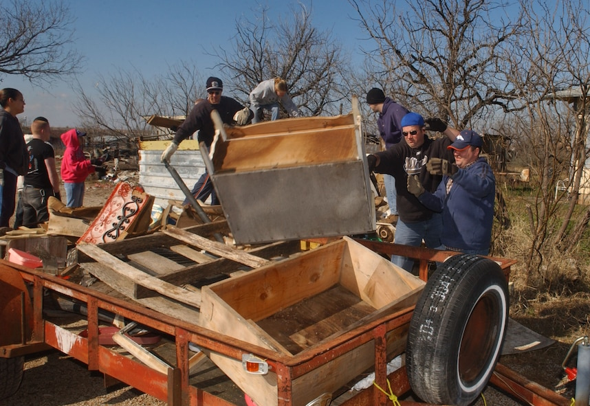 Volunteers toss rubbish onto another trailer during the clean-up. Some of the rubbish included large pieces of furniture and rusty appliances. (U.S. Air Force photo by Staff Sgt. Gina O'Bryan)