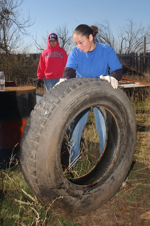 Senior Airman Diana Klesel rolls a large tire out of the way. (U.S. Air Force photo by Staff Sgt. Gina O'Bryan)