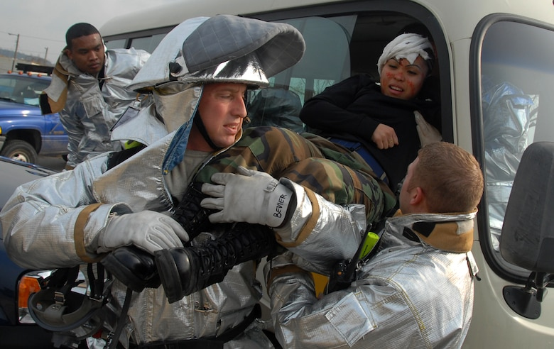 Members of the 8th Fighter Wing disaster response team rescue Staff Sgt. Kim Juliano from a vehicle during a simulated traffic accident Feb. 9. The major accident response exercise on Kunsan Air Base, South Korea, was designed to provide realistic training for emergency response teams and simulated a major vehicle accident with multiple victims.  Sergeant Juliano is assigned to the 8th Communications Squadron.  (U.S. Air Force photo/Tech Sgt. Jeffrey A. Wolfe)