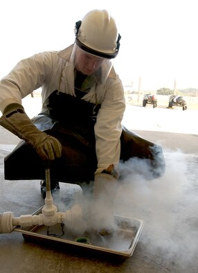 KADENA AIR BASE, Japan -- Senior Airman Christian House, 18th Logistics Readiness Squadron, takes a sample of liquid oxygen to test its smell. If the liquid oxygen gives off a foul odor, the oxygen or the tank itself is bad. This is done every time an oxygen cart is serviced. (U.S. Air Force/Airman 1st Class Kelly Timney)