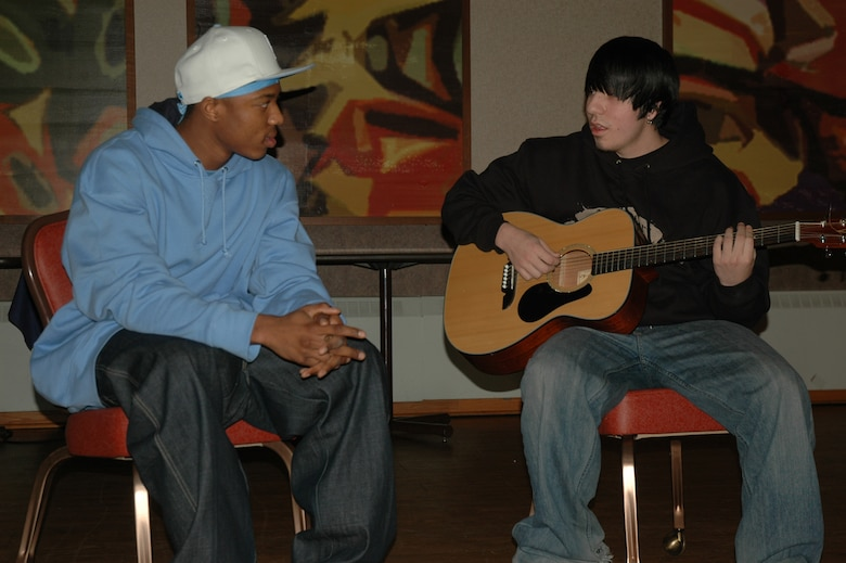 "EIELSON AIR FORCE BASE, Alaska--Airman 1st Class Kristopher Noel, 354th Civil Engineer Squadron fire fighter, raps poems to the guitar riffs of Josh Palos, son of Master Sgt. Robert Palos, 354th Military Equal Opportunity chief, at the Yukon Club during a rehearsal for the street music/hip-hop trio they are in called Moment of Clarity. Not pictured is Ashley Hamilton ""Lady H,"" wife of Airman 1st Class Joseph Hamilton, 354th Security Forces Squadron. The group will perform for Eielson's African American poetry slam 7 p.m Feb. 16 at the Yukon Club and for the African American History Luncheon 11:30 a.m. to 1 p.m. Feb. 28 at the Yukon Club. (U.S. Air Force photo by Airman 1st Class Nora Anton)"