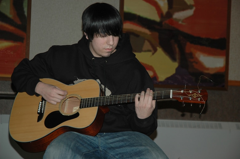 """EIELSON AIR FORCE BASE, Alaska--Josh Palos, son of Master Sgt. Robert Palos, 354th Military Equal Opportunity chief, plays guitar Feb. 9 at the Yukon Club during a rehearsal for the street music/hip-hop trio he is in called Moment of Clarity. Not pictured is Airman 1st Class Kristopher Noel, 354th Civil Engineer Squadron fire fighter, and Ashley Hamilton """"Lady H,"""" wife of Airman 1st Class Joseph Hamilton, 354th Security Forces Squadron.The group will perform for Eielson's African American poetry slam 7 p.m Feb. 16 at the Yukon Club and for the African American History Luncheon 11:30 a.m. to 1 p.m. Feb. 28 at the Yukon Club. (U.S. Air Force photo by Airman 1st Class Nora Anton)"""