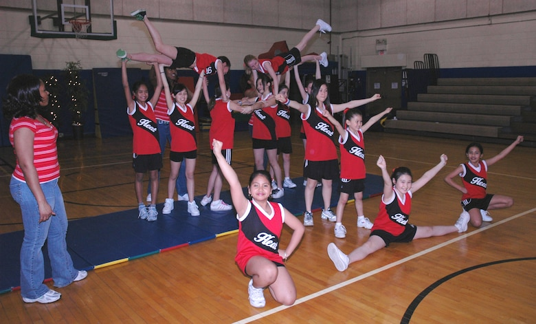"OSAN AIR BASE, Republic of Korea --  Tech. Sgt. Kaleah Hodges (left), cheerleading coach for the Youth Center Sports Program, instructs the girls in how to do the ""pyramid."" The cheerleading squad is for girls from 9-12 years old. (U.S. Air Force photo by Staff Sgt. Benjamin Rojek)"