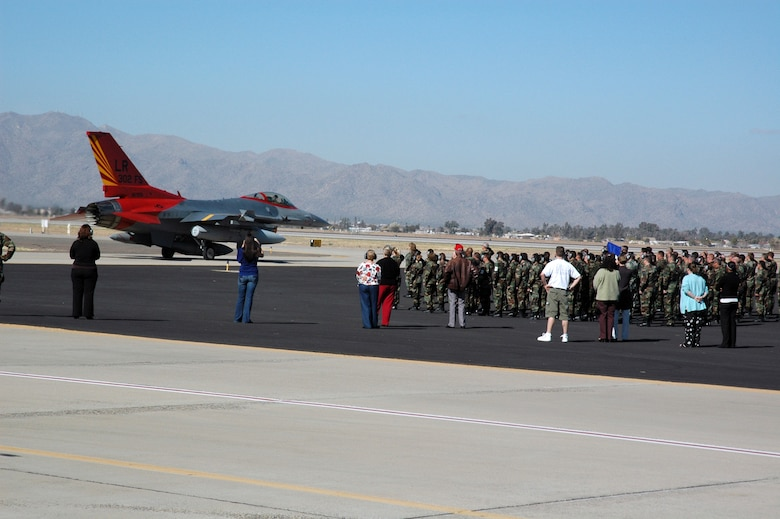 Members of the Air Force Reserve Command's 944th Fighter Wing at Luke Air Force Base, Ariz., watch as the 302nd Fighter Squadron's flagship passes for its final flight. The flagship, painted in original Tuskegee Airmen colors, will go on to become an aggressor at Nellis Air Force Base, Nev. The 944th FW is home to two original Tuskegee Airmen squadrons, the 301st and 302nd Fighter Squadrons. The 944th FW's 17 F-16 Fighting Falcons were reassigned to other units as part of Base Realignment and Closure Commission actions. (U.S. Air Force photo/Staff Sgt. Susan Stout)