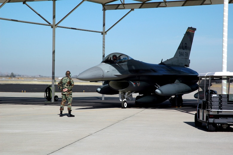 Master Sgt. Bob Rydzynski marshals an F-16 Fighting Falcon for its historic last flight Feb. 12 from Luke Air Force Base, Ariz. The last three F-16s assigned to the 944th Fighter Wing departed Luke as part of Base Realignment and Closure Commission actions. Sergeant Rydzynski is a crew chief at the 944th Aircraft Maintenance Squadron. (U.S. Air Force photo/Staff Sgt. Susan Stout)