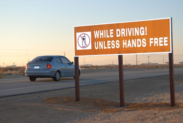 A car passes by a new larger cell phone usage reminder sign at North Gate. The 95th Security Forces Squadron posted the new signs on the base's entrances to better inform the Edwards community and their guests about the base's cellphone policy. (Photo by Senior Airman Jason Hernandez)