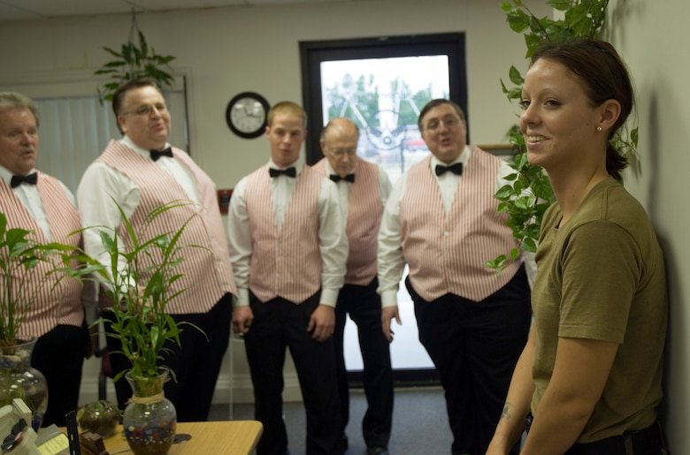 Senior Airman Meredith Hazel, 437th Civil Engineer Squadron, recieves a singing valentine from members of the Charleston Barbershop Chorus Tuesday at the CE complex. Airman Hazel's deployed boyfriend, Senior Airman Tyrone Greer, 437 CES, sent the singing valentine which included two love songs, a long-stemmed rose and  a card. (U.S. Air Force photo/Senior Airman Sam Hymas)