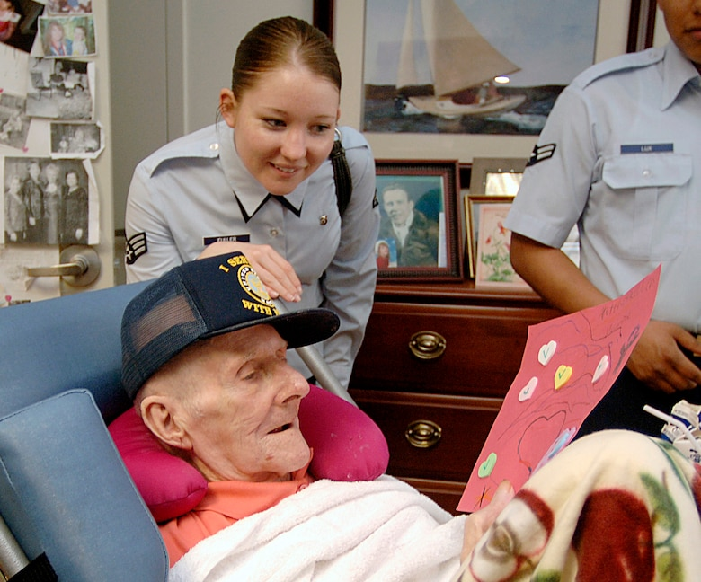Senior Airman Leslie Fuller, 437th Medical Group Bio-environmental Flight, gives Valentine's Day cards made by local school children to William Grady, a Navy veteran who served from 1941 to 1949. (U.S. Air Force photo/Airman 1st Class Nicholas Pilch)