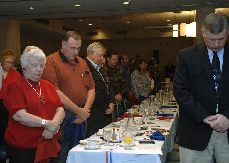 Members of the 49th Fighter Wing bow their heads in prayer during the annual National Prayer Breakfast here Tuesday.