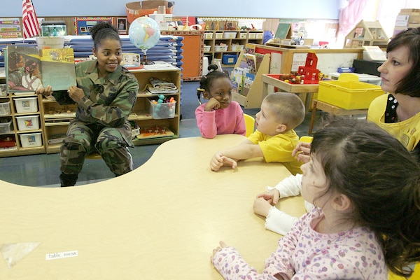Tech. Sgt. Tanesha Lucas, 341st Recruiting Squadron, reads to a group of 3-5 year olds in Luann Ball's yellow room at the Lackland Child Development Center on Lackland Air Force Base, Texas. Sergeant Lucas was one of eight volunteers who spent an hour Feb. 13 reading to children in various classes in the three CDCs on base. The event was organized by the African-American Heritage Committee in honor of African-American History Month. (USAF photo by Robbin Cresswell)