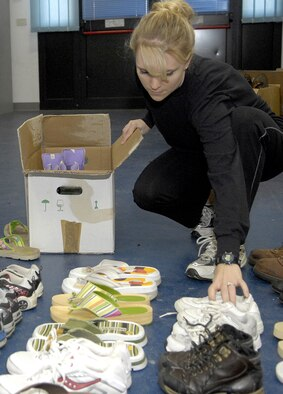 """Capt. Michelle Nevatt, 31st Mission Support Squadron chief of customer support, sorts shoes for the Company Grade Officer's Council shoe drive.  The CGOC delivered 800 pairs of donated shoes and more than 25 bags and boxes of donated clothes to the San Zenone Vescovo church in the Aviano square Monday.   """"The priest explained that every Wednesday the poor come in to receive donated items, such as clothes, shoes and food,"""" said 2nd Lt. Eric Moore, CGOC president. """"He was extremely happy and he wants us to come back with more donations in the future."""" The Aviano Chapel also delivers donations to the Comunita Missionari di Villiaregia located in Pordenone.   (Photo by Airman 1st Class Michael Dorus)"""