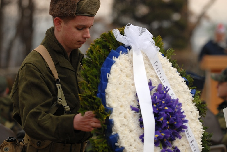 Robert Carter, a member of the Osan American High School Junior ROTC program, moves one of four wreaths that were placed during the Hill 180 ceremony Feb. 9. (U.S. Air Force photo by Airman Jason Epley)
