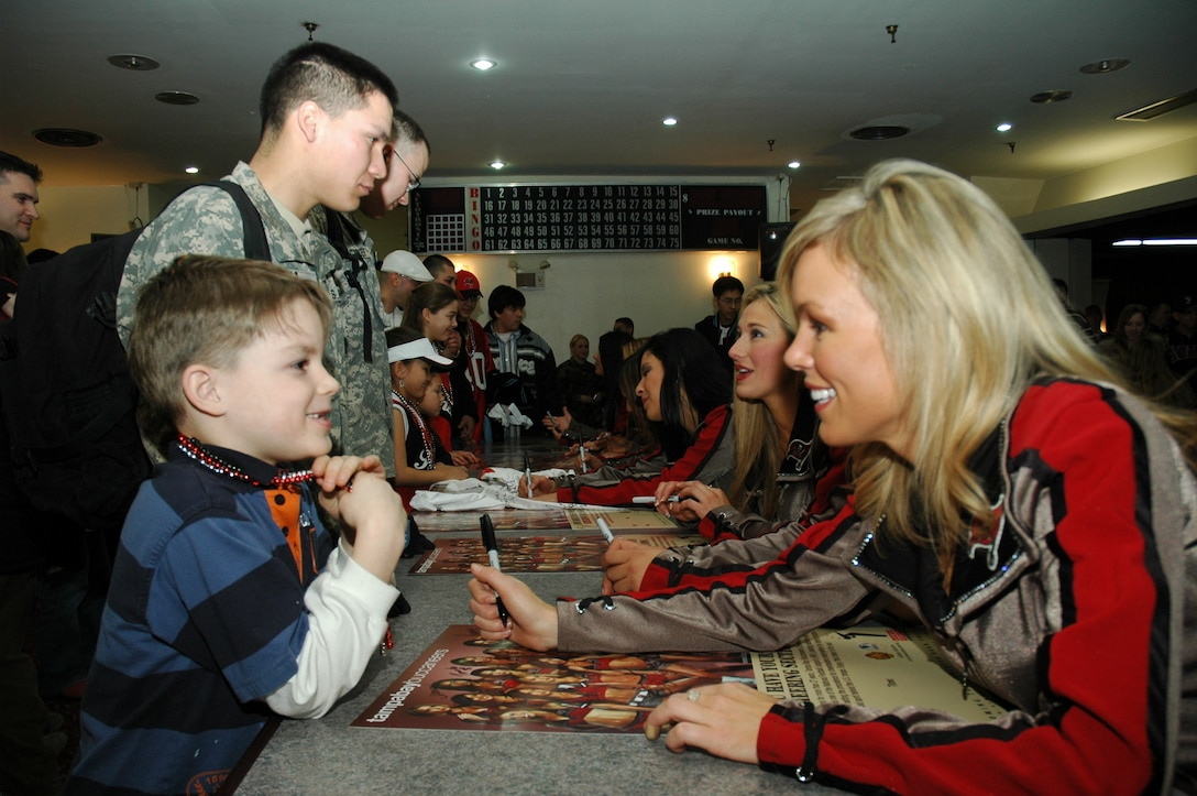 OSAN AIR BASE, Republic of Korea --  Tampa Bay Buccaneers cheerleader Catherine Croake signs an autograph for Trey Hayenga following the cheerleaders' Appreciation Tour 2007 Feb. 14 at the Challenger Club here. The show consisted of various dance and cheer routines followed by a meet-and-greet autograph session with all the cheerleaders. (U.S. Air Force photo by 1st Lt. Kevin Coffman)