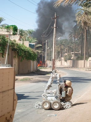 SOUTHWEST ASIA ? Senior Airman Kyle Preece, 332nd Expeditionary Civil Engineer Squadron Explosive Ordnance Disposal flight, works on a F6A robot recently as a vehicle-borne improvised explosive device burns in the background.(U.S. Air Force photo)