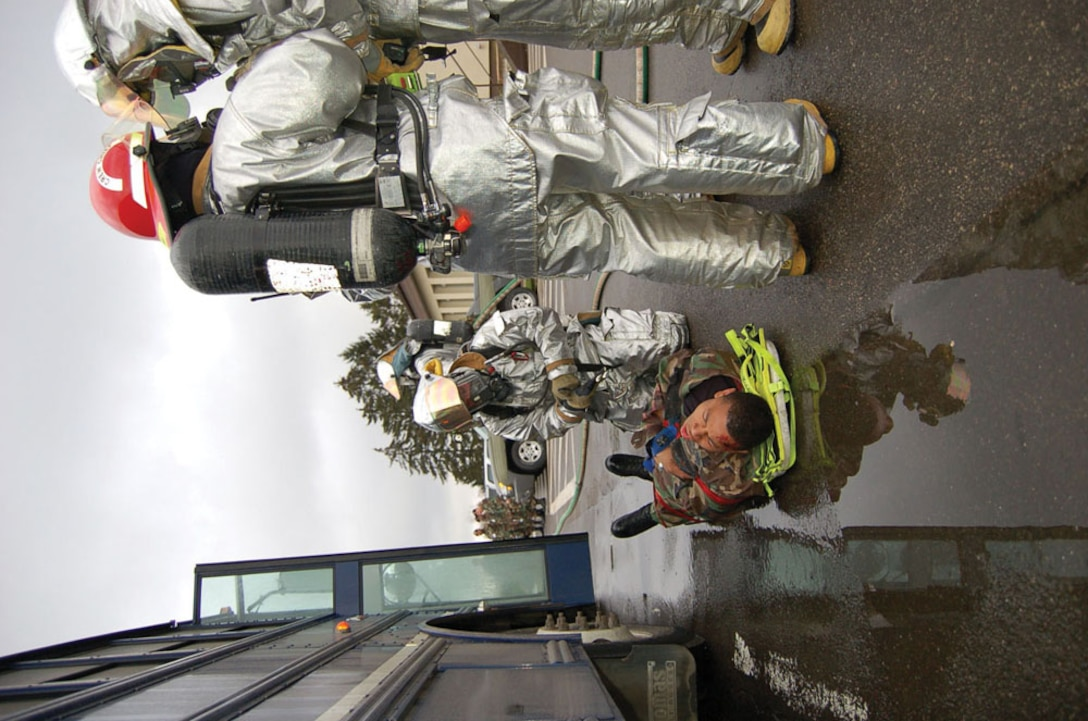 """SPANGDAHLEM AIR BASE, GERMANY -- Firefighters strap a """"victim"""" to a litter during the exercise and prepare to carry him to a safe location.   (US Air Force photo by Senior Airman Eydie Sakura)"""