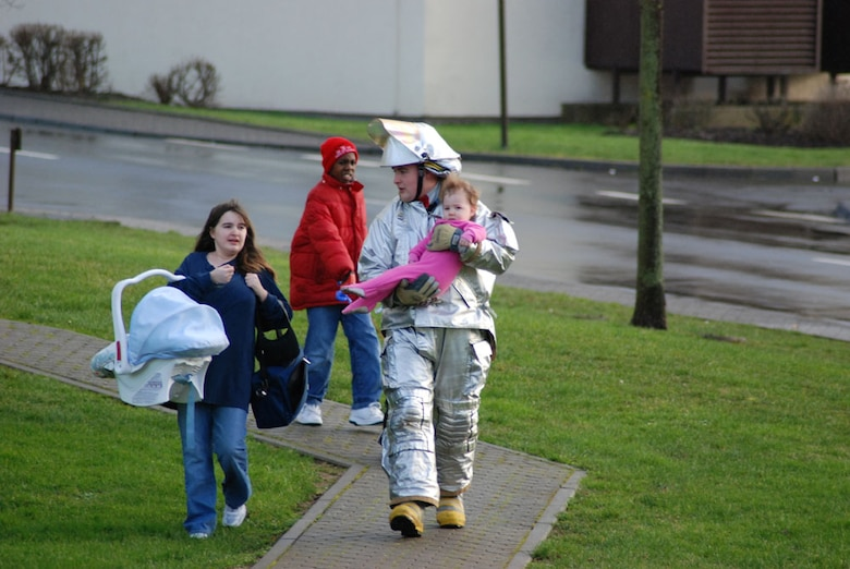 SPANGDAHLEM AIR BASE, GERMANY -- When a suspicious package was found at the Bitburg Annex shoppette Tuesday Matthias Meyer, 52nd Civil Engineer Squadron Fire and Emergency Services Flight fire fighter, helped a woman move her children to a secure area. (US Air Force photo by Nick Anderson)