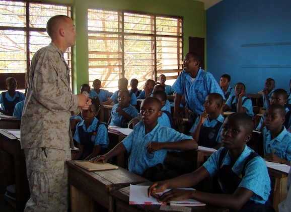 Marines stress importance of education::n::ACCRA, Ghana – Lance Corporal Grant Garab, security forces Marine with the 2nd Fleet Anti-terrorism Security Team, 6th Platoon, leans in to hear a question from a student at the Air Force Base School here Feb. 19. U.S. Marines out of Rota Naval Air Station, Spain, visited the school to answer questions from the students and stress the importance of staying in school. U.S. Armed Forces members are in Accra as part of a joint task force providing infrastructure, aircraft and personnel in support of the President's visits to Benin, Tanzania, Rwanda, Ghana and Liberia Feb. 16 to 21. (U.S. Air Force photo by Tech. Sgt. Denise Johnson)