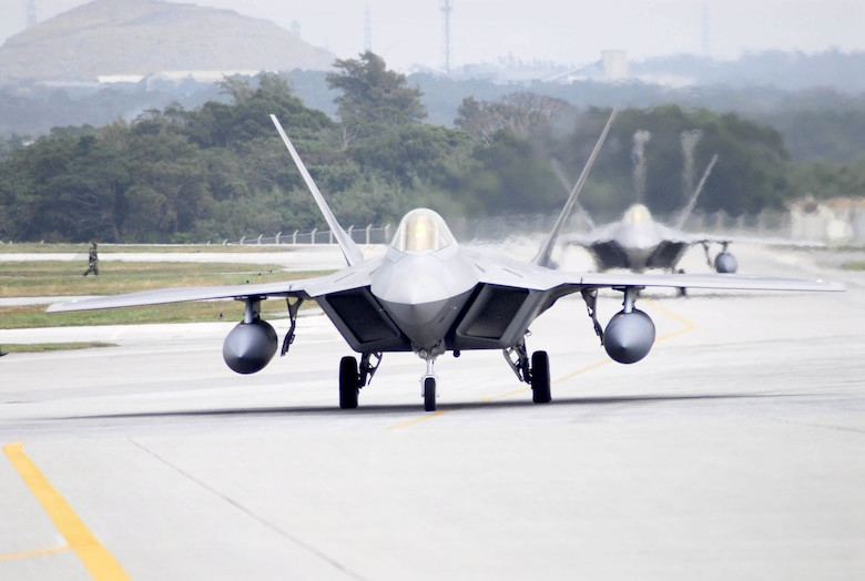 Two F-22 Raptors taxi after landing at Kadena Air Base, Japan, Feb. 18, marking the aircraft's first overseas deployment. The jets are two of 12 along with more than 250 Airmen deployed from Langley Air Force Base, Va., to Kadena as part of an air expeditionary force rotation. (U.S. Air Force photo/Airman Sheila deVera)