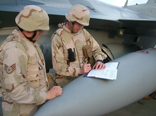 070215--BALAD AIR BASE, Iraq -- Staff Sgt. Jackie Price, 332nd Expeditionary Aircraft Maintenance Squadron, watches as Capt. Jeffrey Campbell, 332nd EAMXS, signs his re-enlistment paperwork Feb. 15 on the flightline. Both Airmen are deployed from the 35th Aircraft Maintenance Squadron at Misawa Air Base, Japan. (U.S. Air Force photo by Senior Master Sgt. Dave Myette)