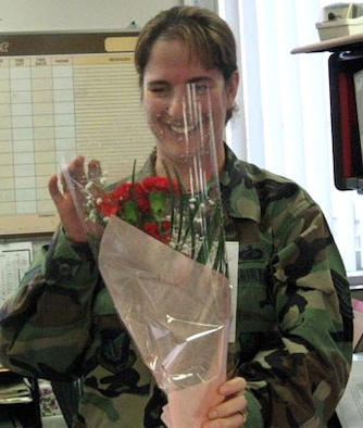 070214 -- MISAWA AIR BASE, Japan -- Tech. Sgt. Colleen Beverly, 35th Comptroller Squadron, receives a bouquet of flowers from her husband Tech. Sgt. Phillip Beverly, 35th Aircraft Maintenance Squadron, who is deployed to Iraq. Volunteers from his squadron delivered 30 personalized cards, 230 roses and 89 carnations to help make the day special for wives, girlfriends and children of deployed Airmen. (Courtesy photo)