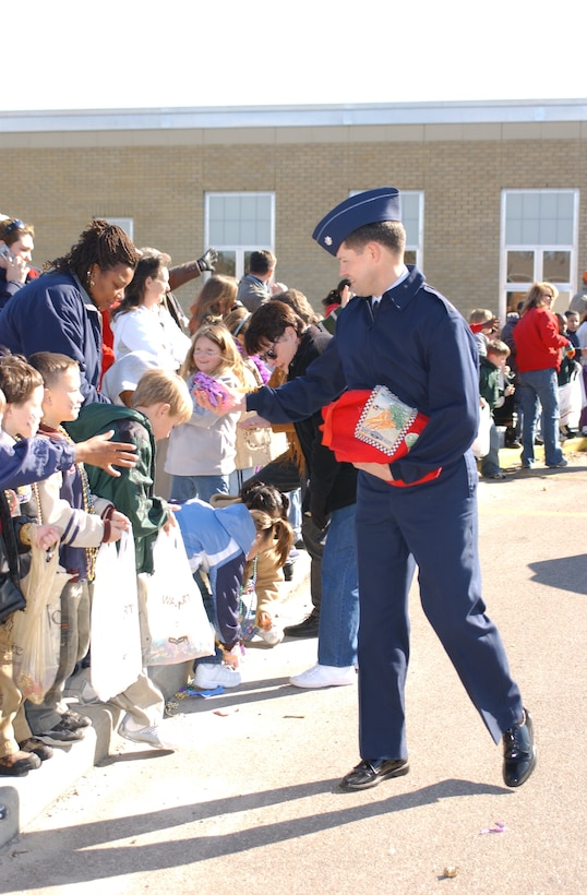 Lt. Col. Paul Valenzuela, 81 Mission Support Squadron commander, Keesler air Force Base, Biloxi Mississippi, hands out candy to students of Beauvoir Elementary School during the schools Mardi Gras parade on 16 February, 2007.  (U.S. Air Force photo by Kemberly Groue)
