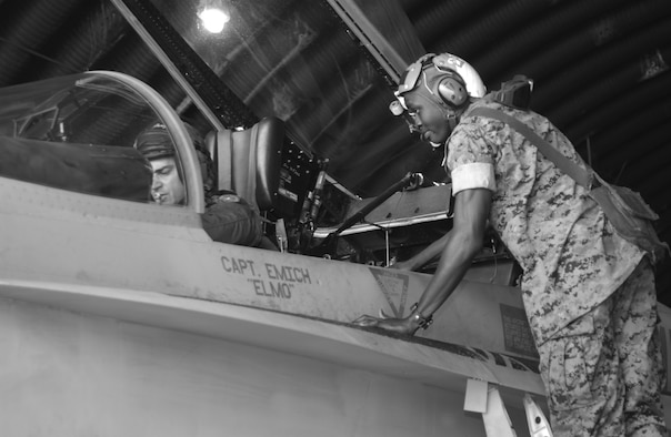 "OSAN AIR BASE, Republic of Korea --  Lance Cpl. Reuben Odoi, plane captain, helps Maj. Clay ""Jungle"" Berardi prepare the cockpit for start up. (U.S. Air Force photo by Airman 1st Class Gina Chiaverotti)"