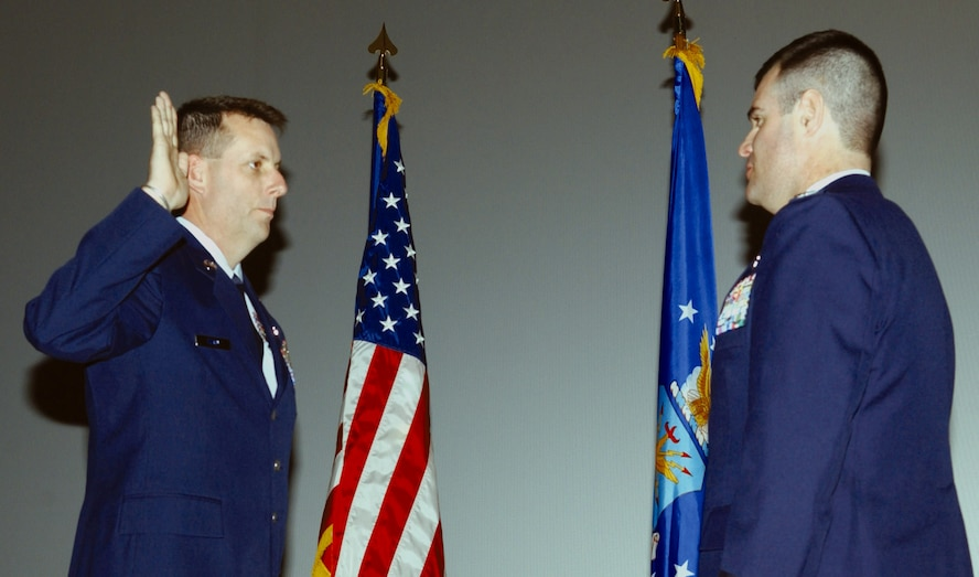 Col. Scott Bethel, 17th Training Wing commander (right), administers the Oath of Enlistment to Chief Master Sgt. (select) Darryl Furby, the superintendent of the 314th Training Squadron (left), at a recognition ceremony for the new Chief Feb. 9 at the base theater. (U.S. Air Force photo by Airman 1st Class Kamaile Chan)