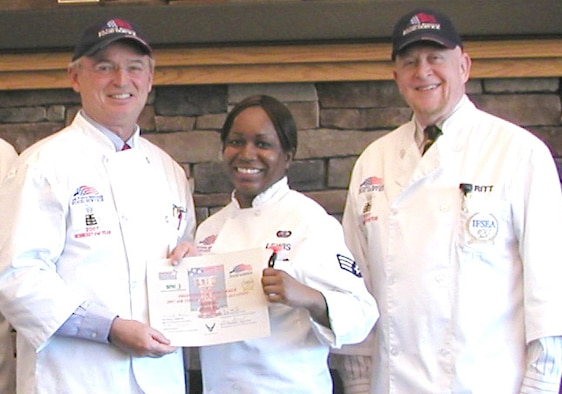 Michael Gibbons (left), National Restaurant Association, and Art Ritt, International Food Services Executives Association, present Senior Airman Donice Lewis, Warrior Inn midnight shift leader, with a Professional Performer Award certificate. Mr. Gibbons and Mr. Ritt, both John L. Hennessy evaluators, visited Fairchild this week to evaluate the 92nd Services Squadron's food services operations. (Courtesy photo)