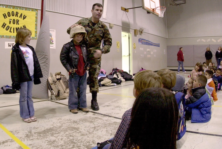 """(Left): Col. Scott Bethel, 17th Training Wing commander, helps six-year-old Hunter Herd, a student at Holiman Elementary School, put on a desert camouflage uniform helmet. The student was one of a handful of school children that the commander invited to try out some of his deployment gear. """"Our students need great role models in their lives, said Judy Bragg, Holiman's principal. """"To meet a high ranking hero and hear from him the importance of education, leadership, and American pride was a blessing,"""" Judy Bragg, Holiman Elementary School principal said. Col. Bethel was invited as part of a joint program between the school and Paul Ann Baptist Church. Called Project Impact, the program aims to enhance the lives of the school children through special presentations and encouraging words from motivational speakers. (U.S. Air Force photo by Airman 1st Class Luis Loza Gutierrez)"""
