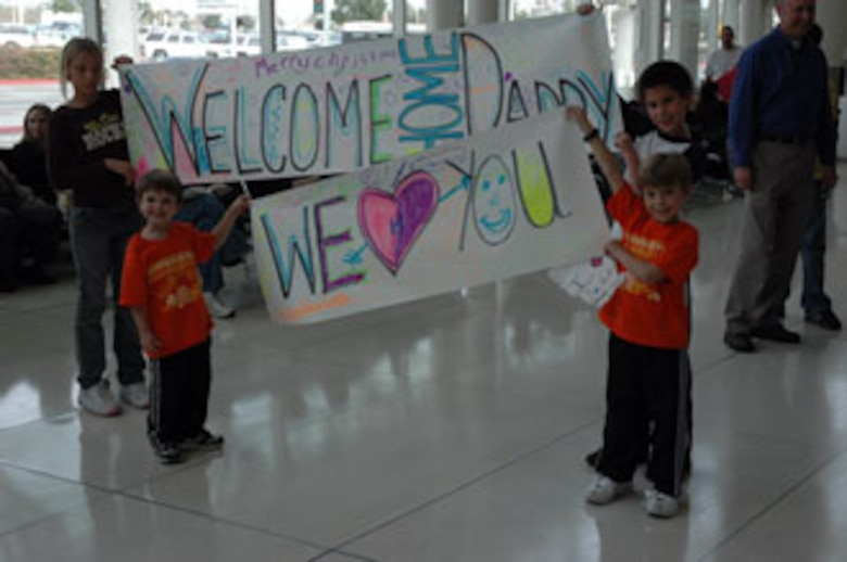 Anxious family members hold banners in anticipation of their father's arrival.  The children were waiting at Ontario Airport with other 163rd RW members and families. (U.S. Air Force photo by Maj. Brenda Hendricksen)