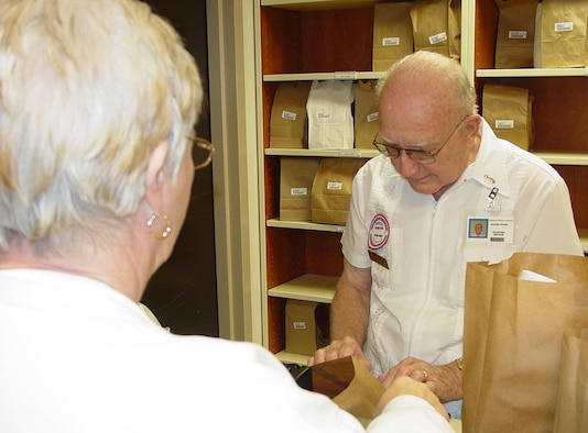 Keesler Medical Center volunteer Grover Stuart hands a prescription to a patient in the main pharmacy.  Mr. Stuart, a retired senior master sergeant, has been providing assistance in the facility for 15 years.  He's one of approximately 70 people serving as medical center volunteers.   Emily Shelton, volunteer supervisor, said this is fewer than half the people on the rolls before Hurricane Katrina.  More volunteer help is needed as additional services return to the facility, she noted.  For more information, call Mrs. Shelton, 388-6841 or 669-2263.  (U.S. Air Force photo by Steve Pivnick)