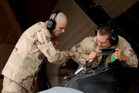Staff Sgt. Adrian Abram, left, and Tech. Sgt. Travis Topel, 332nd Expeditionary Aircraft Maintenance Squadron, change the cockpit light assembly on an F-16 at Balad Air Base, Iraq. Sergeants Abram and Topel are both deployed from Aviano Air Base, Italy in support of Operation Iraqi Freedom. (Photo by Staff Sgt. Michael Holzworth)