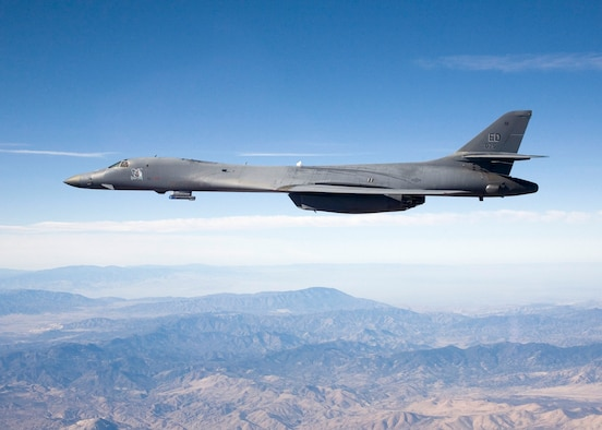 A B-1B Lancer carries the Sniper pod on its belly as it flies over Edwards' skies during a flight test here. The 419th Flight Test Squadron testers recently concluded the initial development of the Sniper pod installed on a B-1B here recently. The Sniper pod is an advanced targeting pod with a multi-sensor system that increases the aircraft's self-targeting capability. (Photo by Steve Zapka)