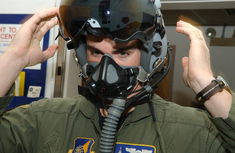 EIELSON AIR FORCE BASE, Alaska -- Captain Jeremey Wimer, 18th Fighter Squadron F-16 pilot, tries on a newly issued flight helmet while gearing up Feb. 21 at the 18th Fighter Squadron. The new helmet mounted queing system has targeting technology that projects holographic data on the inside right of the visor in the form of a container, or que and allows pilots to continually survey and distinguish between friendly and enemy air and ground targets. ( U. S. Air Force phot by Airman 1st Class Christopher Griffin.)