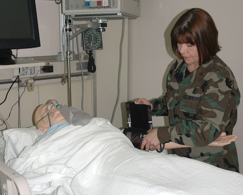MINOT AIR FORCE BASE, N.D. -- Maj. Ann Perry, 5th Medical Group education and training/readiness flight commander performs a blood pressure check on a SimMan at the skills lab here Feb. 23. A SimMan is a portable and advanced patient simulator for medical training. Major Perry recently won the Air Force's 2006 education and training nurse award. (U.S. Air Force photo by Airman 1st Class Wesley Wright)