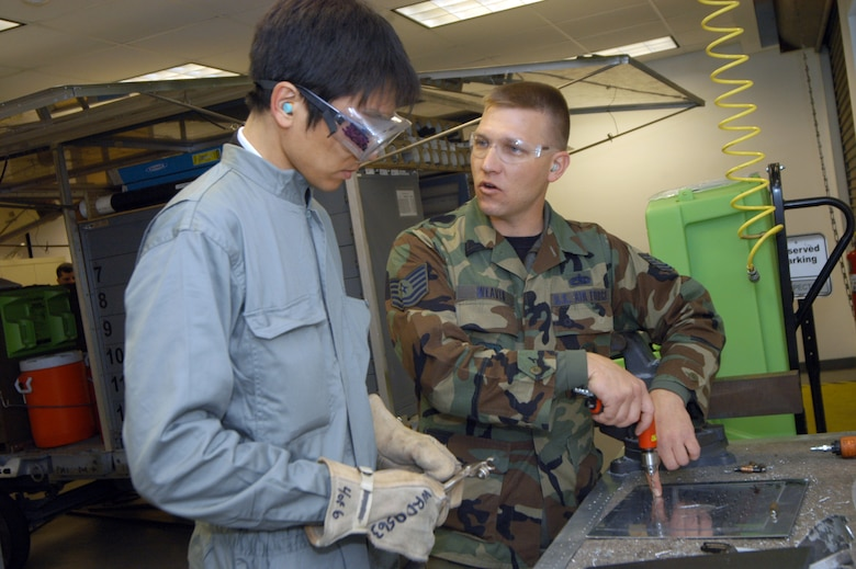 Tomohiro Matsuo, the civilian member among the students, gets instruction from Tech. Sgt. Glen Weaver, 653rd Aircraft Battle Damage Repair training instructor.